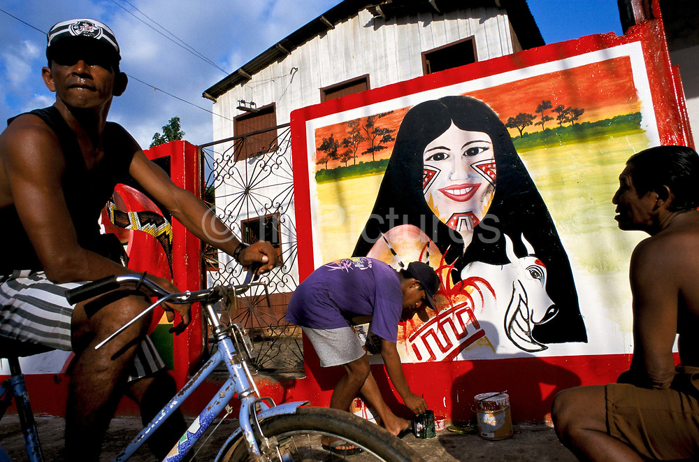 """A man paits a wall mural of the """"Cunha Poranga"""", the queen of the """"Boi Bumba"""" Carnival, Parintins, Brazil. The carnival serves to celebrate and re-enact Indian traditions and perpetuate myths and legends. It has evolved over time and involves the battle between to opposing bulls, known as Garantido and Caprichoso."""