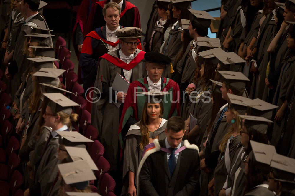 University leaders process through rows of young graduates wearing rented gowns and mortarboards in the central hall of their university, at the start of their graduation ceremony, on 13th July 2017, at the University of York, England.