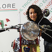 PADOVA, ITALY - OCTOBER 27:  A woman checks her make up in the mirror of  vintage Guzzi motor bike on October 27, 2011 in Padova, Italy. The Vintage and Classic Cars Exhibition of Padova, running from the October 28 - 30, is the most important European trade show for vintage cars and motorbikes, showcasing over 1600 vehicles.