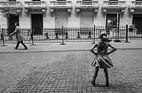 """""""Fearless Girl"""" by artist Kristen Visbal confronts the New York Stock Exchange as a determined man rushes by."""