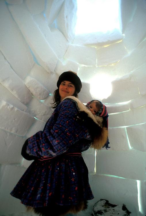 Barrow, Alaska. Inside an igloo, mom Luciana Aikins carries daughter Juliana on her back in the traditional Iñupiaq style. MR