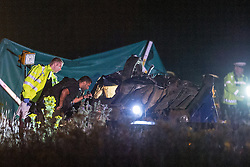 © Licensed to London News Pictures . 21/07/2014 . Nottinghamshire , UK . Police examine the interior of an overturned car at the scene . Police , fire crew and ambulances on the A1 road in Ranby yesterday morning (21st July 2014) following a fatal multi vehicle accident . Leroy and Sheila Carrington (aged 68 and 58) died at the scene when the Peugot 206 they were driving collided with a Vauxhall Astra . Roderick Franks (58) , who was a passenger in the Astra , died in hospital , following the crash . The road was closed in both directions whilst police investigated the scene .  Photo credit : Joel Goodman/LNP