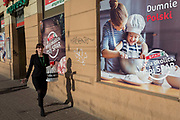 A young modern Polish women walks and smokes a cigarette, passing a poster outside a Spar supermarket that shows the stereotyping of gender: a mother and her daughter enjoying baking in the kitchen together, on 23rd September 2019, in Krakow, Malopolska, Poland. The poster translates as: My neighborhood ,my spar.