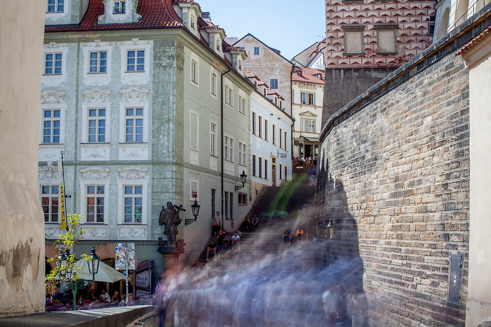 """Crowds walking down from Prague Castle towards the Townhall Stairs """"Radnicke schody"""" in the back and """"Nerudova street"""" on the left."""