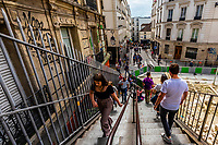 People climbing steep stairs up the Butte Montmartre (hill), Paris, France.