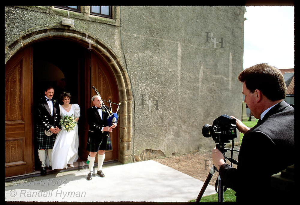 Photographer snaps photos of bride, groom and bagpiper as they exit church doors; Anstruther. Scotland