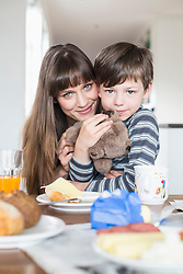 Portrait of mother and son at breakfast table, smiling