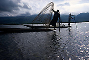 Inle Lake. Villager rows his boat with the distinctive style of the Intha leg rowers, wrapping one leg around the oar. The style developed as it was necessary to stand while rowing in order to see over the heavy growth of vegetation. Burma 1999