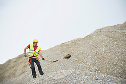 Construction worker throwing stone using shovel at site, Munich, Bavaria, Germany, Europe