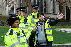 Pro-Brexit campaigner James Goddard in his 'gilet juane' asks police to remove a placard that he says offends him as he once again visits and attempts to disrupt Steve Bray's SODEM anti-Brexit protest the day after he was seen harassing former cabinet minister Anna Soubry. Westminster, London, December 20 2018.
