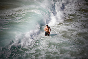 Portuguese Summer. Man play with the waves at Azenhas do Mar beach in Sintra.