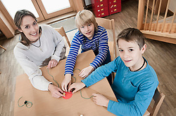 Portrait of two playing boys and female childcare assistant
