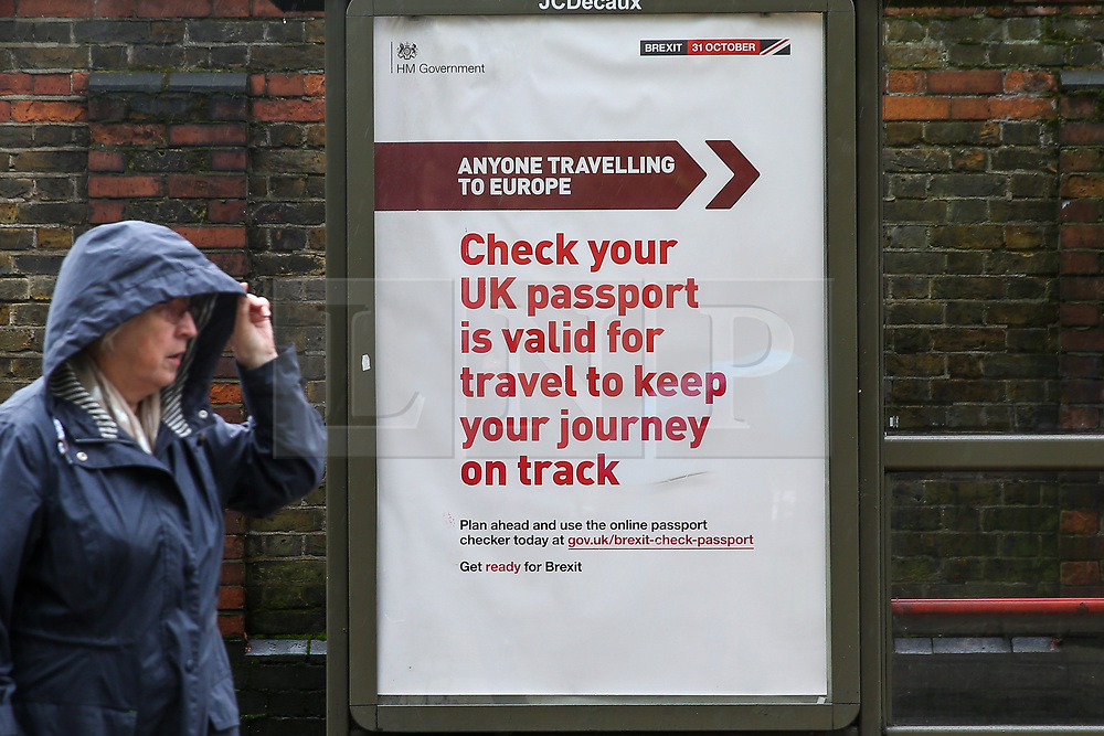 """© Licensed to London News Pictures. 11/10/2019. London, UK. A member of the public walks past the latest Brexit poster advert featuring 'Anyone Travelling to Europe"""" displayed at a bus stop in north London, with twenty days to Brexit day. The Get ready for Brexit campaign is costing £100m, preparing the nation to depart the EU. British passport holders are urged to ensure they have at least six months validly on their passports to travel to Europe after Brexit. Passport validity rules will become tighter if there is a no deal. Photo credit: Dinendra Haria/LNP"""