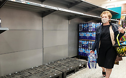 © Licensed to London News Pictures. 21/09/2021. London, UK. A shopper wearing a face covering walks past empty shelves of sparkling bottled water in Morrisons, north London, Fears of food shortages grow after two of the UK's biggest Carbon Dioxide (CO2) producers halted production last week due to soaring gas prices. UK food producers and supermarkets are warning that shoppers are likely to face food shortage caused by a lack of gas could hit this week. Photo credit: Dinendra Haria/LNP