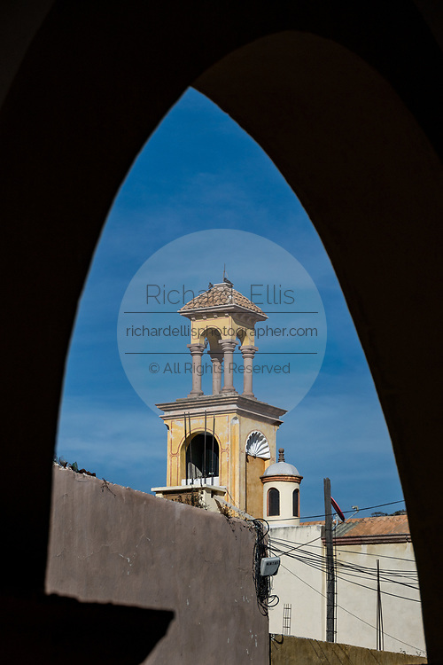 A decorative tower framed in an archway in the beautiful colonial village of Bernal, Queretaro, Mexico. Bernal is a quaint colonial town known for the Pena de Bernal, a giant monolith which dominates the tiny village is the third highest on the planet.
