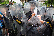 24 MAY 2014 - BANGKOK, THAILAND:  A woman protesting the Thai coup scuffles with police at a roadblock in Bangkok. There were several marches in different parts of Bangkok to protest the coup that unseated the popularly elected government. Soldiers and police confronted protestors and made several arrests but most of the protests were peaceful. The military junta also announced that firing of several police commanders and dissolution of the Thai Senate. The junta also changed its name from National Peace and Order Maintaining Council (NPOMC) to the National Council for Peace and Order (NCPO).   PHOTO BY JACK KURTZ