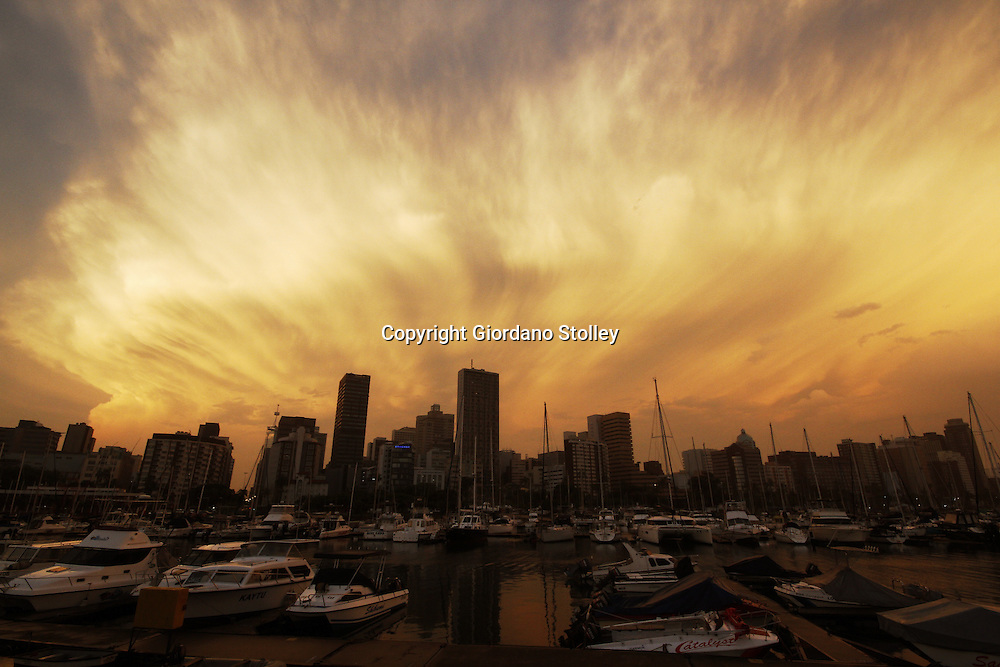 DURBAN - 31 October 2013 - The setting sun catches the clouds of a storm as it moves over Durban's harbour and out to sea. Picture: Allied Picture Press/APP