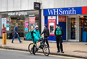 25th February 2021, Cheltenham, UK. A member of the local council in conversation with a Deliveroo rider during the third national lockdown in cheltenham High Street.