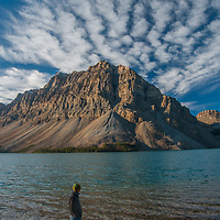 A wading hiker watches as dramatic clouds soar over Crowfoot Mountain and Bow Lake in Banff National Park, Alberta, Canada.