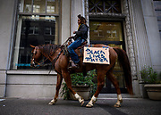 """Brianna Noble, 25, rides her horse that holds a sign that reads """"Black Lives Matters"""" in downtown Oakland at the start of a protest remembering Minneapolis man, George Floyd on Friday, May 29, 2020."""