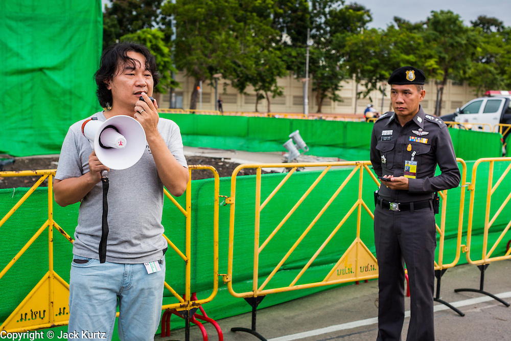 """24 JUNE 2014 - BANGKOK, THAILAND: A Thai police officer (right) listens to a poet at a meeting of the Monsoon Poets Society in Bangkok. Members of the """"Monsoon Poets Society"""" gathered in front of the Anantasamakom Throne Hall Tuesday to pay homage to the People's Party, a Siamese (Thai) group of military and civil officers (which became a political party) that staged a bloodless coup against King Prajadhipok (Rama VII) and changed Thailand (then Siam) from an absolute monarchy to a constitutional monarchy on 24 June 1932. Since the coup against the civilian government on 22 May, the ruling junta has not allowed political gatherings. Although police read the poems, they did not arrest any of the poets or make any effort to break up the gathering.     PHOTO BY JACK KURTZ"""