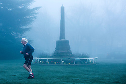 "© Licensed to London News Pictures. 14/03/2014. Meriden, Coventry, UK. Dense fog covered the Midlands earlier today. Pictured, a jogger makes his way past the ""Centre of England"" monument in Meriden, near Coventry. Photo credit : Dave Warren/LNP"