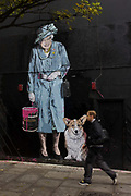 Queen holding paint can and pet corgi dog mural by artist Mr Brainwash at the Old Sorting Office, New Oxford Street, London. Mr. Brainwash is the moniker of Los Angeles-based filmmaker and Pop artist Thierry Guetta.
