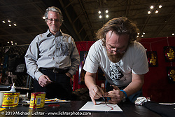 Harley-Davidson's head of motorcycle design Ray Drea has some fun with Blaster of Italy as they do side-by-side pin-striping during the Annual Mooneyes Yokohama Hot Rod and Custom Show. Japan. Sunday, December 7, 2014. Photograph ©2014 Michael Lichter.