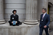A City businessman walks through Bank as environmental activists protest about Climate Change during the blockade outside the Bank of England in the heart of the capitals financial district, the City of London aka the Square Mile, on the seventh day of a two-week prolonged worldwide protest by members of Extinction Rebellion, on 14th October 2019, in London, England.