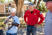"""Wyoming Game and Fish game warden Jim Seeman, center, and retired Game and Fish biologist Bud Stewart, right, look on as Ahalt uses her mouth to tighten the strings of a hood on the head of a red-tailed hawk on the shoulder of Marshall Street in Manderson, Wyoming on Wednesday, Sept. 4, 2019. Ahalt met Seeman and Stewart halfway between Cody and Buffalo to rescue the hawk, which had been discovered in Buffalo, Wyoming, earlier that day, unable to fly. Ahalt named the hawk """"Speedy"""" after the speeding ticket she narrowly avoided upon her arrival in town. The police officer who pulled her over was going to write her a ticket until Ahalt introduced herself as """"the Bird Lady"""" and explained that she was in town on official Game and Fish Department business. The officer let her off with a warning."""