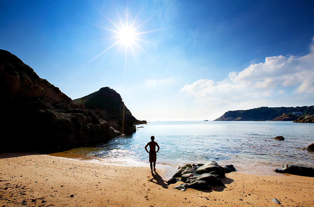 Man standing at the shoreline of a hidden cove in the St Brelade area of Jersey's south coast.