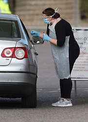 EDITORS NOTE: NUMBER PLATE PIXELATED BY PA PICTURE DESK Medical staff taking samples at 10.04am at an NHS drive through coronavirus disease (COVID-19) testing facility at Chessington World of Adventures, in Greater London, as the UK continues in lockdown to help curb the spread of the coronavirus.