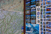Detail of postcard souvenirs of a map and Dolomite mountain scenes in a shop selling tourist memorablia on Passo Falzarega (Pass) in south Tyrol, Italy.