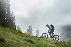 Man with Pedelec riding uphill in mountains, Saalfelden, Tyrol, Austria