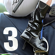 A jockey positions his boots in the horses stirrup during a day at the Races at the Gore Race Meeting, Gore, Southland, New Zealand. 18th December 2011. Photo Tim Clayton