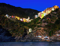 """""""The San Pietro bell tower shines at twilight over Corniglia""""...<br /> <br /> I began my daily journey at the northern most town of Monterosso and took the train to the southernmost town of Riomaggiore. I sailed up the coast photographing each Cinque Terre town along the way aboard the Angelina Dada. Upon arriving back home in Monterosso, soft light illuminated the sky and azure sea of the Mediterranean convincing me to sail all the way back to Riomaggiore with my gracious guides Claudio and Eddie of """"Cinque Terre dal Mare"""" sailing excursions. We arrived just in time for a perfect sunset. After a nice dinner...I caught the last train at midnight back home to Monterosso. A very long day, but worth every minute! This image of Corniglia, the only Cinque Terre town not directly on the sea…was taken at the beginning of the journey from Riomaggiore. The two image panorama of this tiny village seems to snuggle into the Cliffside basking in the evening sunlight."""