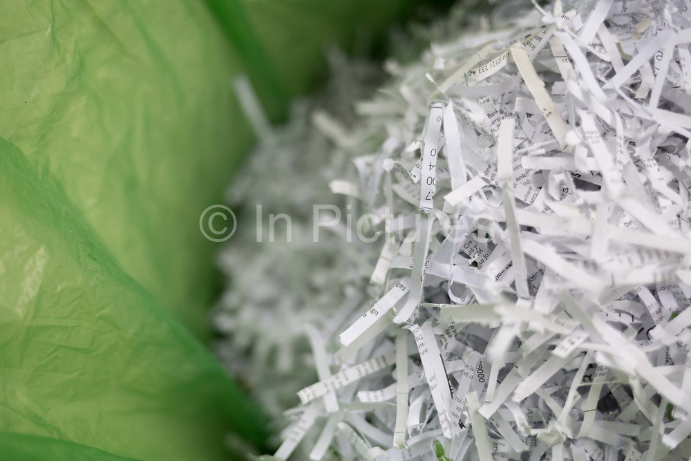 A detail of shredded domestic documents and paperwork in a waste paper bin lined with green polythene bag, a precaution against identity theft and to ensure ones personal data is protected from fraud, on 12th June 2020, in London, England.