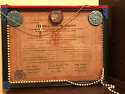 Framed –Ordination certificate with beads and pearls and blue Mardi Gras buttons <br />