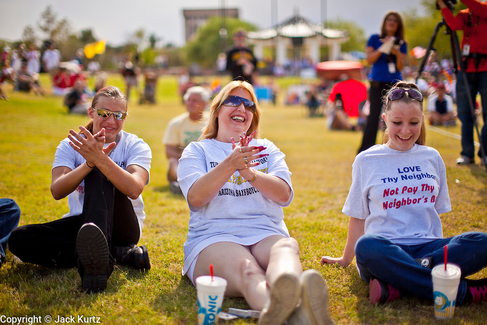12  JUNE 2010 - PHOENIX, AZ: Nick McCannon, 15, his mom, Chez McCannon and his sister, Kaylene McCannon, 17, from San Diego, CA, cheer for Congressman Steve King (R-IA) during his speech at the rally in support of SB 1070 at Bolin Memorial Park near the State Capitol in Phoenix Saturday. About 500 people, many from California and Florida, attended the afternoon rally. PHOTO BY JACK KURTZ