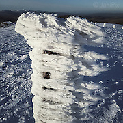 Wind-blown snow formations on an isolated post near the summit of Arening Fawr, Snowdonia