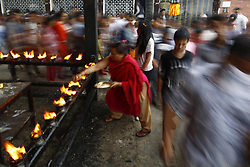 August 17, 2017 - Kirtipur, Nepal - A devotee lights oil lamp as others circle while offering prayers around Bagh Bhairav temple during Bagh festival in Kirtipur, Nepal on August 17, 2017. It is believed that devotees who circle the Bagh Bairav temple 108 times will be blessed with good health and success during the ritual festival. (Credit Image: © Skanda Gautam via ZUMA Wire)