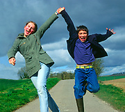 AF5CP1 Twin boy and girl jumping for joy holding hands as they run along a country road. Image shot 2006. Exact date unknown.