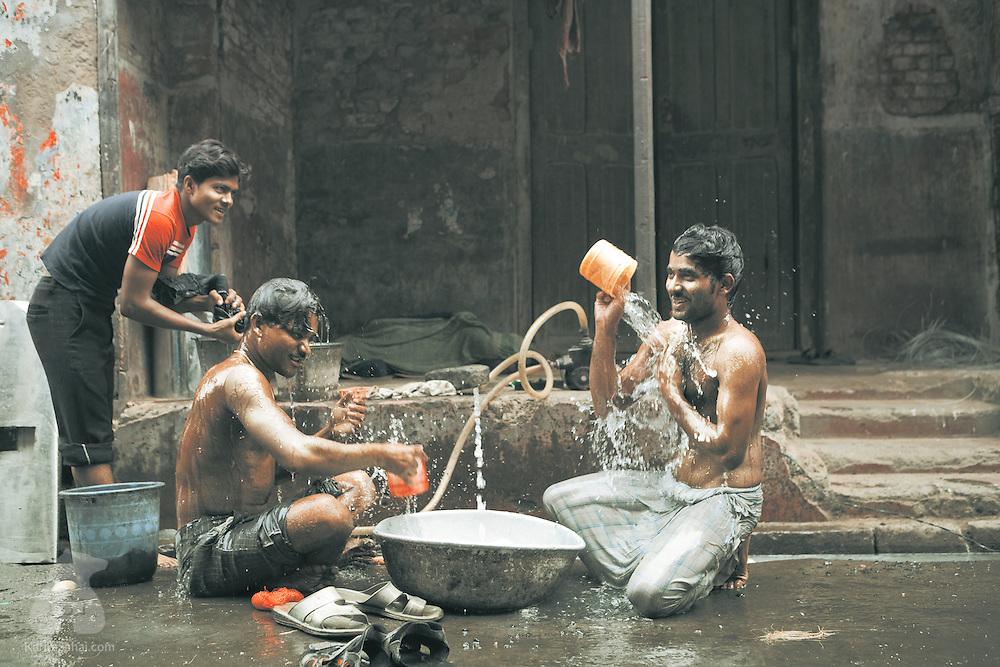 Men washing in street, Kolkata, West Bengal, India.