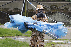 © Licensed to London News Pictures. 24/04/2018. Salisbury, UK. A member of the armed forces carries plastic wrapped tools after removing contaminated soil in the area at the Maltings where a bench was earlier removed as the cleanup operation begins in Salisbury. Former Russian Spy Sergei Skripal and his daughter Yulia were poisoned using a nerve agent in the city last month. Experts have warned that 'Toxic levels' of the nerve agent novichok could still be present at hot spots around the city. Photo credit: Peter Macdiarmid/LNP