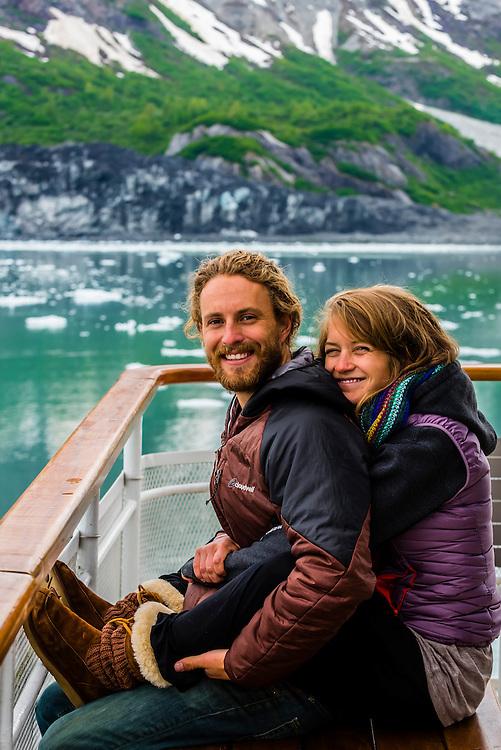 Couple enjoy the scenery of Glacier Bay National Park (Margerie Glacier in background) aboard the Un-Cruise ship Wilderness Explorer, southeast Alaska USA.