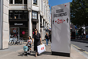 A lady walks past a social distance post with a young girl pushing a child's pram, on Oxford Street during the Coronavirus pandemic, on 20th August 2020, in London, England
