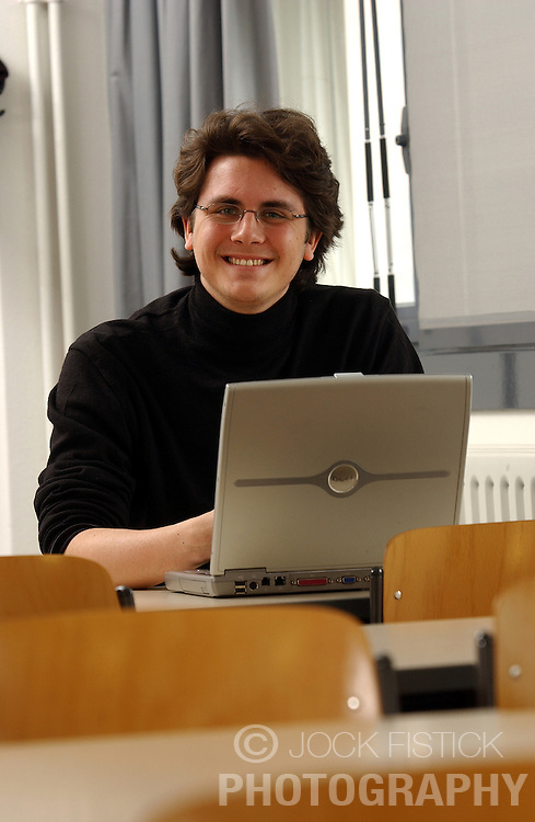 PARIS -  FRANCE - APRIL-21-2004 - Smiling young male business student using a wireless - wifi - laptop computer. <br /> <br /> technology - business - computer - wifi - wireless - internet - communication - email - www - world wide web - web surfing - connect - connecting - connected - connectivity - study - studying - research - academics - education - student - university - young - adult - male - man - think - thinking - concentrate - concentration - concentrating - model released - laptop - notebook - smile - smiling