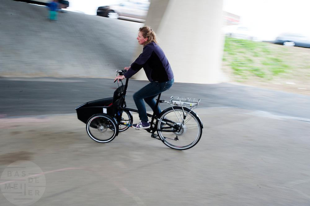 Een vrouw probeert een bakfiets met trapondersteuning uit. In Nijmegen vindt voor de derde keer het International Cargo Bike Festival plaats. Het tweedaags evenement richt zich op het gebruik en de gebruikers van bakfietsen. Bakfietsen worden in heel Europa steeds vaker ingezet, zowel door particulieren als bedrijven. Het is een duurzame vorm van transport en biedt veel voordelen.<br /> <br /> In Nijmegen for the third time the International Cargo Bike Festival is hold. The two-day event focuses on the use and users of cargobikes. Cargo bikes are increasingly being deployed across Europe, both individuals and businesses. It is a sustainable form of transport and offers many advantages.Nederland, Nijmegen, 13-04-2014