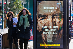 """© Licensed to London News Pictures. 29/01/2021. London, UK. Women walk past the government's 'Look him in the eyes - And tell him the risk isn't real.' publicity campaign poster in north London. Covid-19 infection rates are continuing to drop across London. But health experts are warning Londoners to follow the lockdown rules, as """"any relaxation would risk a rapid reversal or decline."""" Photo credit: Dinendra Haria/LNP"""