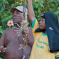 A local fisherman and his grandson show off their catch of the day, a huge Caribbean spiny lobster (Panulirus argus) in Manzanillo, Costa Rica on April 6, 2009. (Photo/William Byrne Drumm)